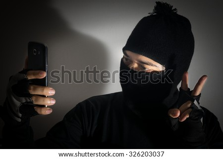 Robber man self portrait with smart phone. - stock photo