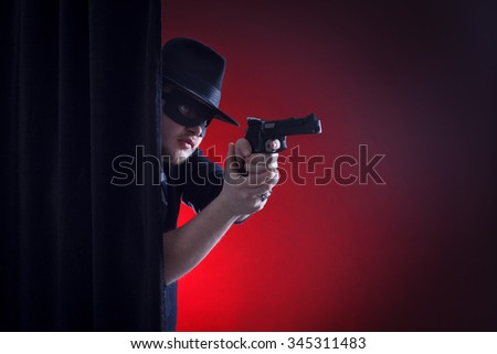 robber or bandit in a mask shoots a gun. - stock photo