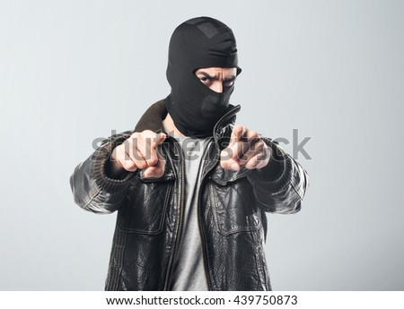 Robber pointing to the front over grey background - stock photo