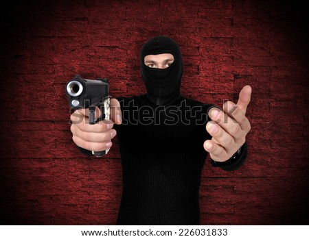 robber with gun in hand on red background - stock photo