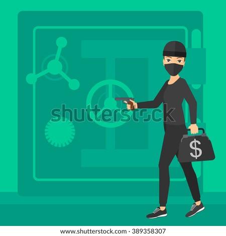 Robber with gun near safe. - stock photo