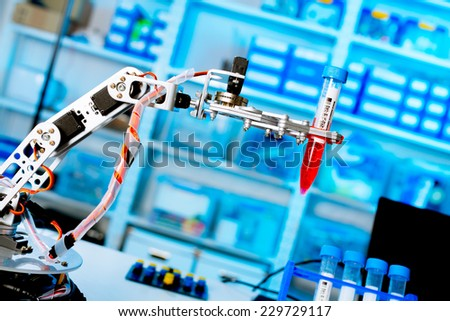 robot manipulates chemical tubes in the laboratory - stock photo