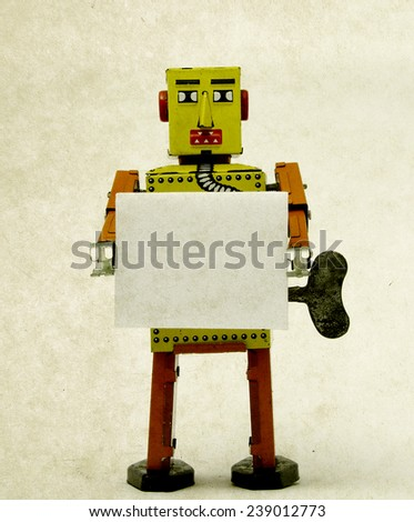 robot toy holding a sign  - stock photo
