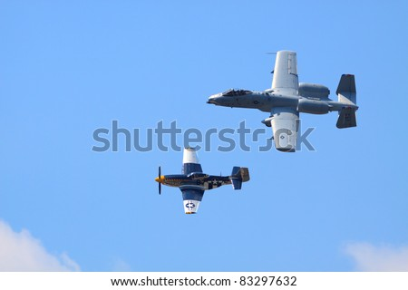 ROCHESTER - JULY 17: A WWII era P-51 Mustang fighter airplane and a current-model A-10 Thunderbolt ground attack airplane flying in formation at an airshow in Rochester, NY on July 17, 2011. - stock photo