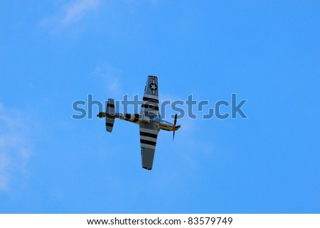 ROCHESTER, NY - JULY 17: A WWII era P-51 Mustang fighter airplane flying during a performance at an airshow in Rochester, New York on July 17, 2011. - stock photo