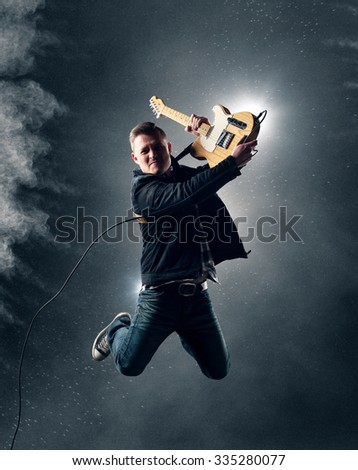 Rock and Roll Guitarist jumping with electric guitar with smoke and powder in background - stock photo