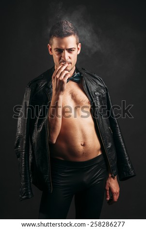Rock and roll musician smoking cigarette - stock photo