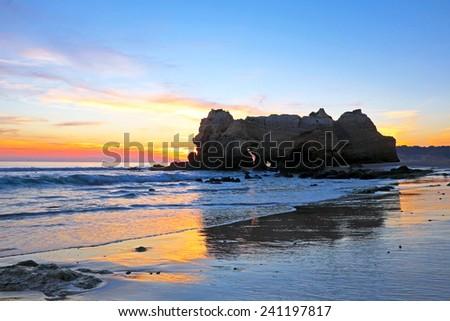 Rock at Praia da Rocha Portimao in the Algarve Portugal at sunset - stock photo