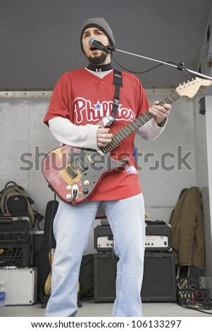 Rock band guitarist with Philadelphia Phillies baseball top playing music in front of Citizens Bank Park, opening game, March 31, 2008 of the Philadelphia Phillies Major League Baseball team. - stock photo