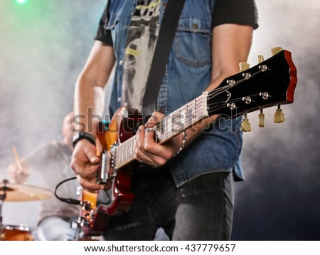 Rock band performs on stage. Guitarist, bass guitar and drums. The guitarist plays solo. - stock photo