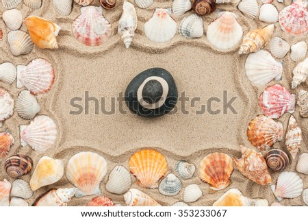 Rock cairn on the sand among sea shells, top view - stock photo