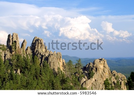 Rock cliffs and Fluffy Clouds - stock photo