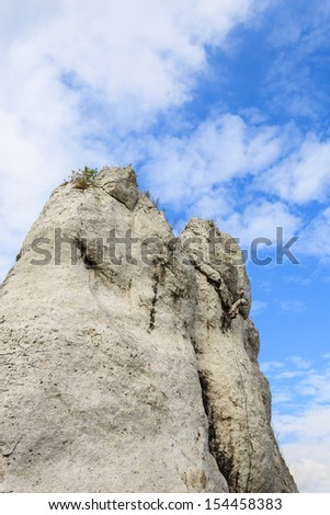 Rock climber climbing in Jura Plateau near Jerzmanowice village, Poland - stock photo