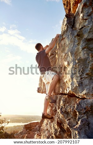 Rock climber climbing up a steep piece of mountain with copyspace - stock photo