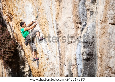 Rock climber on a face of a cliff  - stock photo