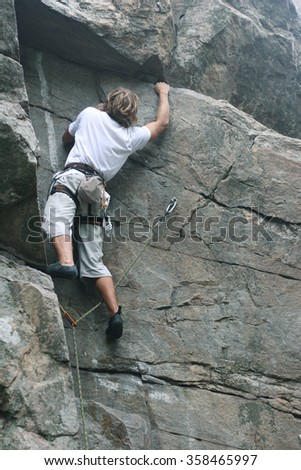 Rock climber preparing to the next move on his way - stock photo