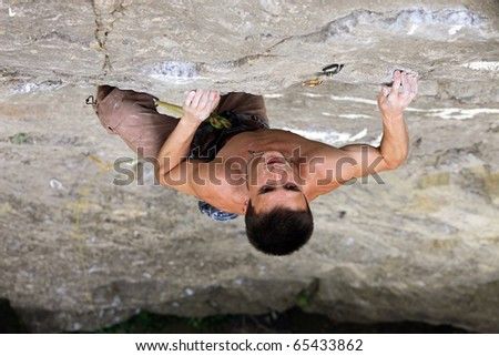 Rock climber preparing to the next move on his way up to the top of the cliff - stock photo