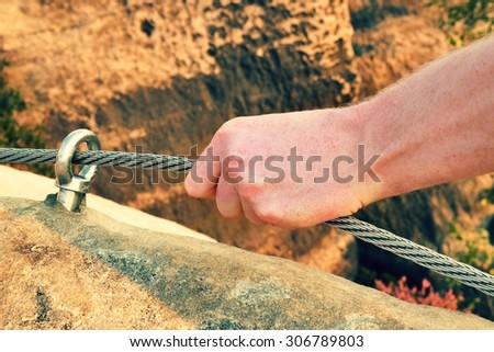 Rock climber's hand hold on steel twisted rope at steel bolt eye anchored in sandstone rock. Tourist path via ferrata. - stock photo