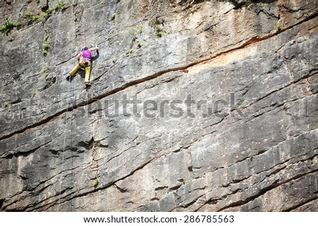Rock climber stretching for hold on vertical climb with copy space - stock photo