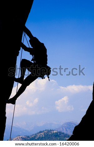 Rock climber works his way up a sheer rock face in the Sequoia National Park. - stock photo
