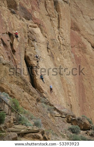 Rock climbers and belayers on sheer cliff,Smith Rock State Park, Central Oregon - stock photo