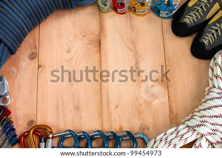 Rock climbing gear theme depicting a blue rock climbing dynamic rope, set of cams, climbing shoes, static rope, quickdraw carabiners, locking carabiners, set of climbing nuts, and a ATC belay device. - stock photo