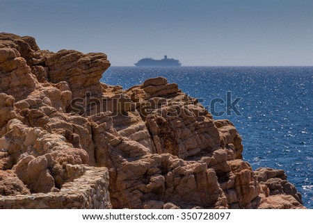 Rock Coast of the Costa Brava with a cruise ship passing by in the distant haze - stock photo