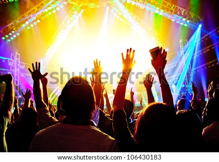 Rock concert, happy people silhouettes, raise up hands, disco party with large group of dancing man, bright colorful stage lights, active lifestyle, music entertainment, nightclub, night life concept - stock photo