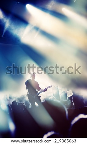 Rock concert stage. Guitarist playing on electric guitar. - stock photo