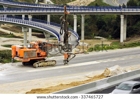rock drilling caterpillar vehicle in highway construction site - stock photo