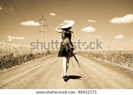 Rock girl with guitar at countryside. Photo in old yellow color image style. - stock photo