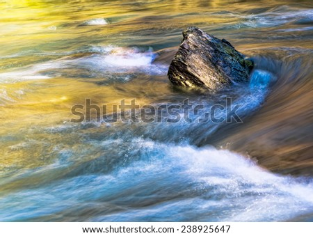 Rock holding firm, rough waters - stock photo