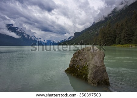 Rock in foreground of serene sky above Chilkoot Lake.  Location is Haines, Alaska, United States.  Horizontal image with copy space.  Excellent salmon fishing in this Southeast Alaska area.  - stock photo