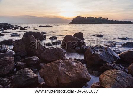 Rock in sea beach at sunset  - stock photo