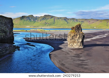 Rock in the sand. Cape Dirholaey in southern Iceland. On the beach with black volcanic sand is a huge rock  - stock photo