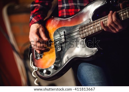 Rock music background, bass guitar player, closeup photo with selective focus and motion blur effect  - stock photo