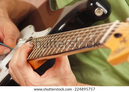 Rock musician put fingers for chords on electric guitar closeup - stock photo