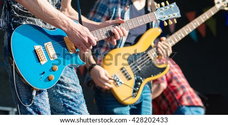 Rock musicians playing at live stage. - stock photo