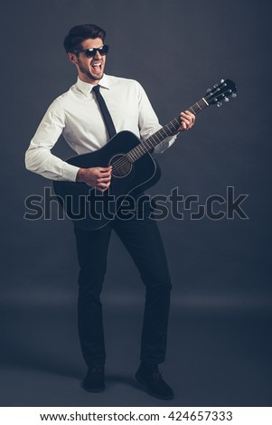 Rock or business star? Full length of handsome well-dressed young man in sunglasses playing guitar and keeping mouth open while standing against grey background - stock photo