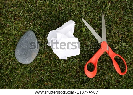Rock, paper, scissors, on grass - stock photo