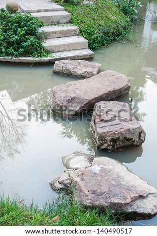 Rock path way in the small river of urban park. - stock photo