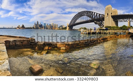 rock pool in Sydney harbour in a foreground of CBD view across water with skyscrapers and Bridge's arch in panoramic layout - stock photo