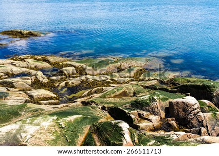 Rock shoreline and blue water. - stock photo