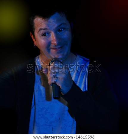 Rock singer on a scene singing rock in ecstasy (flirting with the audience) - stock photo