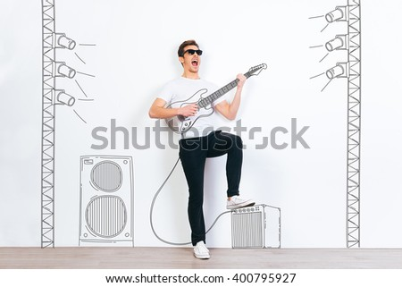 Rock star! Young handsome man in sunglasses playing drawn guitar and keeping mouth open while standing against white background with illustration of stereo column and stage light  - stock photo