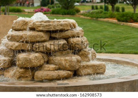 Rock Waterfall Flowing Water into a Pool - stock photo