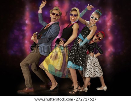 Rockabilly family band having fun posing with guitar and dancing  in 1950s style clothing  - stock photo