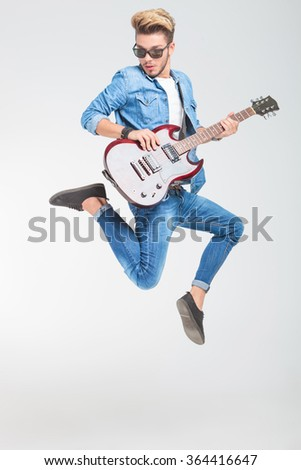 rocker jumping one side in studio while playing guitar and looking down  - stock photo