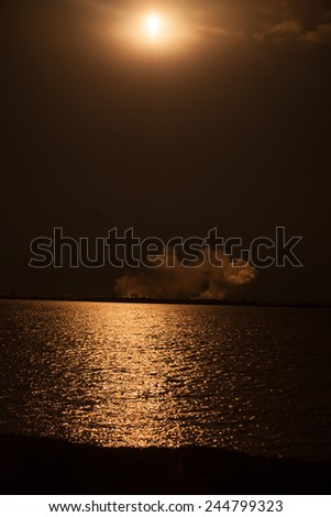 Rocket being launched into outer space at night, and reflecting on water - stock photo