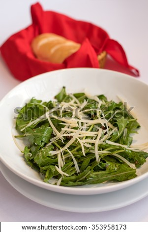 rocket salad with parmesan cheese served with bread in red basket (soft focus on salad) - stock photo